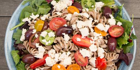 A bowl of pasta salad topped with vegan tofu feta