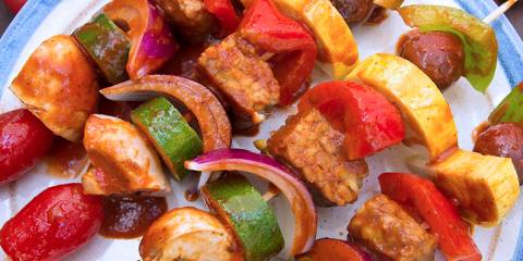 A plate of skewered vegetables and tempeh
