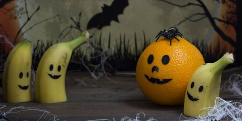 Bananas and an orange with jack-o-lantern smiles on them. Halloween backdrop.