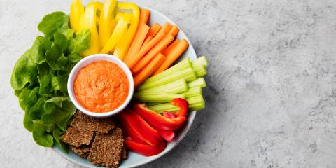 Assorted fresh vegetables with Roasted Red Pepper & Almond Dip. Stone background