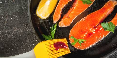 salmon being slathered with sauce for the grill