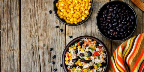 Fiesta salad, corn and black bean displayed in separate bowls. On a rustic farm table.