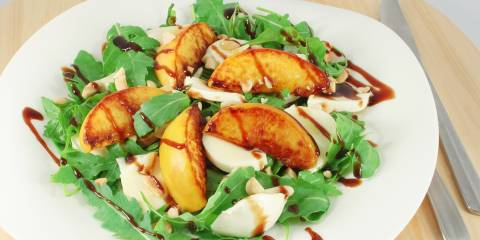 A plate of arugula with peaches and mozzarella