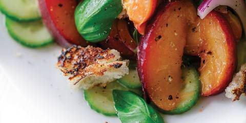 A close up image of Peach Panzanella on a white plate.