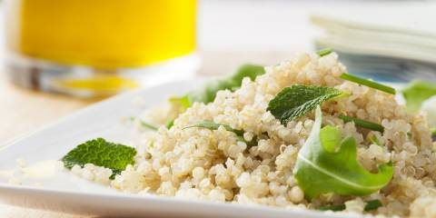 Quinoa with green leaves in white dish