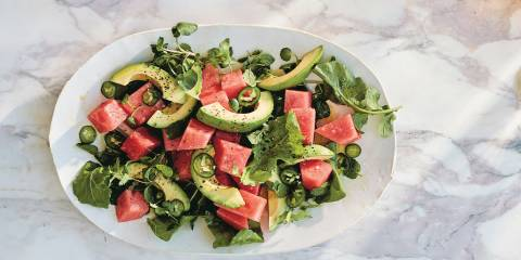 Top view of Spicy Watermelon Salad on a white platter on a white marble background.