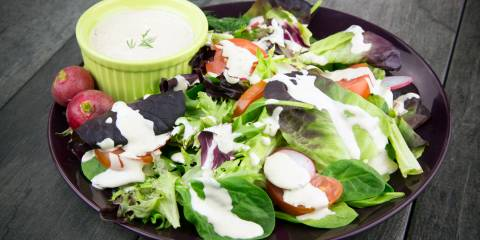 A bowl of salad drizzled with Tahini Dill dressing.