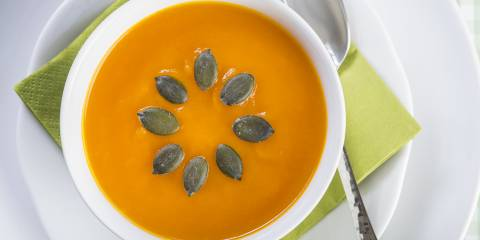 Creamy pumpkin soup, in a white bowl, decorated with seeds in a sunburst pattern.