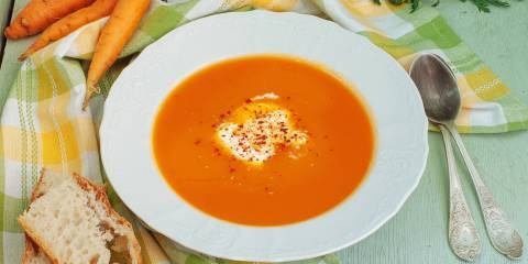 A bowl of carrot and apple soup with bread on the side