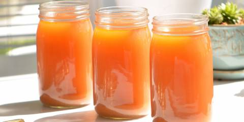 Three mason jars filled with homemade detox broth on a table in the sunlight.
