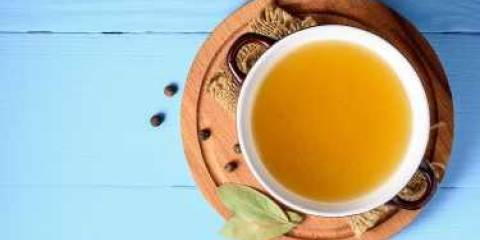A top view of a pot of Homemade Chicken Broth on a blue background.
