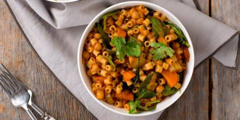 Spicy Ditalini and Chickpea Stew in a white bowl on a wooden table.