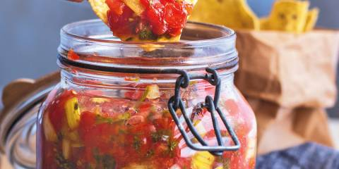 A tortilla chip dipped in a jar of fermented garden salsa