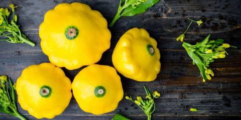 Yellow patty pan squash on wooden background.