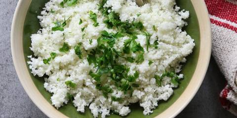 A bowl of grated cauliflower with rosemary.