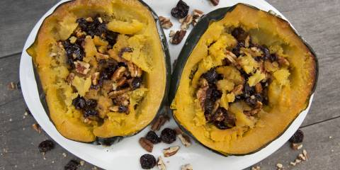 A plate of acorn squash stuffed with berries and pecans