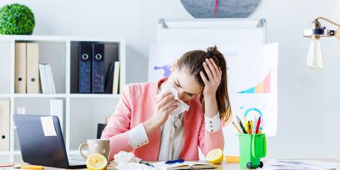 a young woman sick but at the office anyway