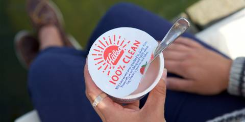 a woman eating yogurt with that claims to be 100% clean
