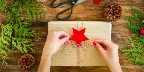 tying a string bow on a gift wrapped in craft paper.