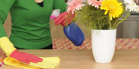 a woman wiping down a table with all-natural cleaning supplies