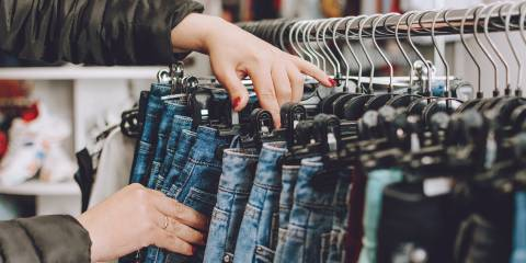 Woman shopping and choosing a pair of jeans off a clothing rack.