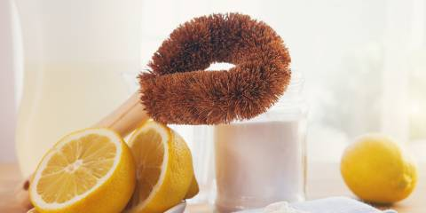 Eco-friendly natural cleaning products, bamboo brush, lemon, baking soda sodium bicarbonate on wooden table.