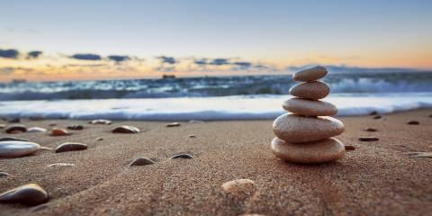 Stones balanced on a beach at sunrise