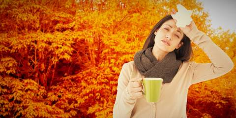 A sick woman holding a mug and a tissue in autumn
