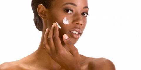 Woman moisturizing skin