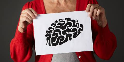 An older woman holding up an illustration of a brain