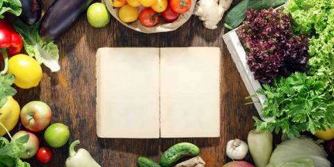 A blank notebook on a rustic table surrounded by fruits and vegetables.