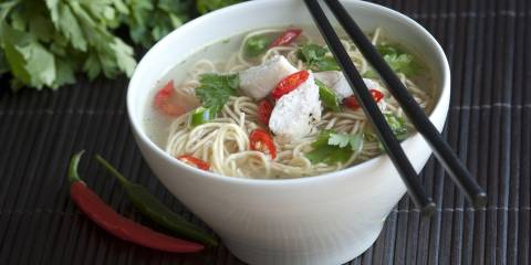 Bowl of asian chicken noodle soups with chopsticks.