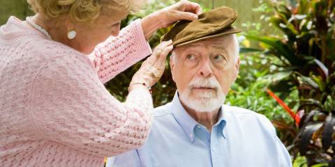 A senior woman putting a hat on her husband