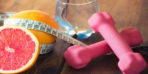 Weight loss concept with tape measure organic grapefruit, pink dumbbells and natural bottle of water