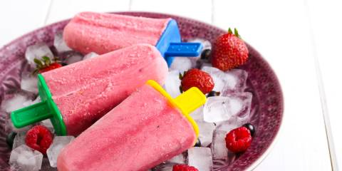 Some strawberry and blueberry lemonade popsicles staying frosty on a tray of ice