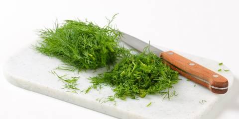 Sprigs of fresh dill on a cutting board