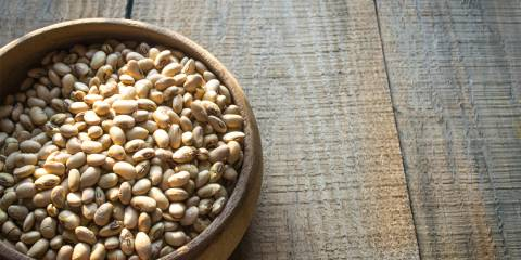 A natural wood bowl of roasted soy beans