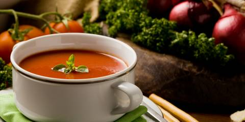 a bowl of soup surrounded by fresh vegetables