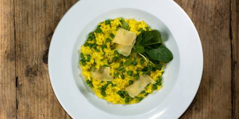A bowl of leek and pea risotto with garnish and cheese