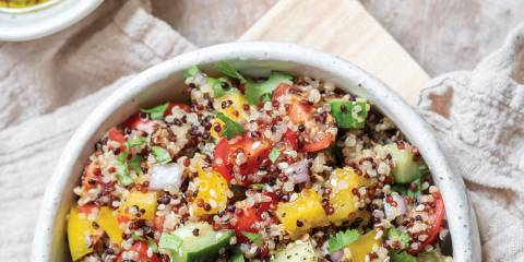 Top view of Quinoa Tabbouleh in a white bowl on flour sack cloth