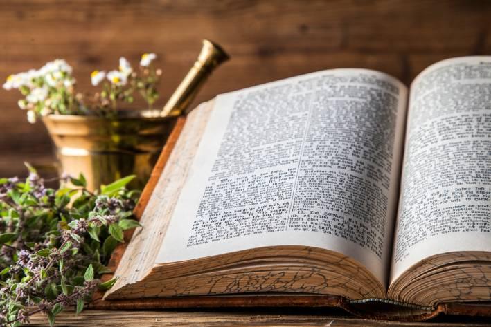 Ancient natural medicine, herbs and old herbal medicine book.