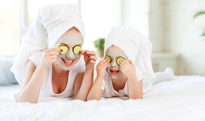 Mother and child with natural face masks on, covering eyes with cucumber slices.