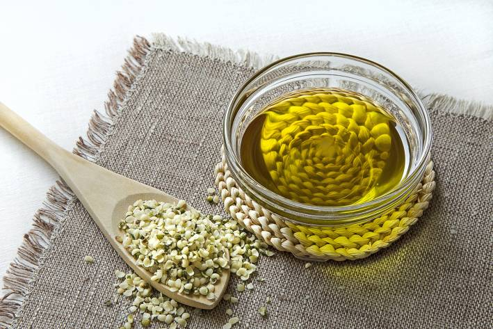 A spoonful of hemp seeds and a bowl of hemp seed oil