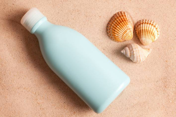 A bottle of sunscreen in the sand
