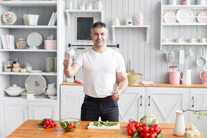 Middle-aged athlete, cuts vegetables salad of cucumber and tomato.