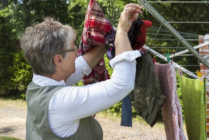 A senior woman hanging laundry out to dry
