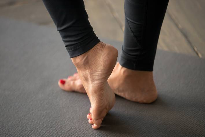 A woman doing stretches to strengthen muscles in the foot and ankle.