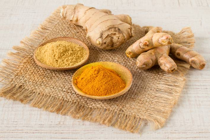 Turmeric and Ginger root on a jute mat next to small spice dishes filled with powdered versions.