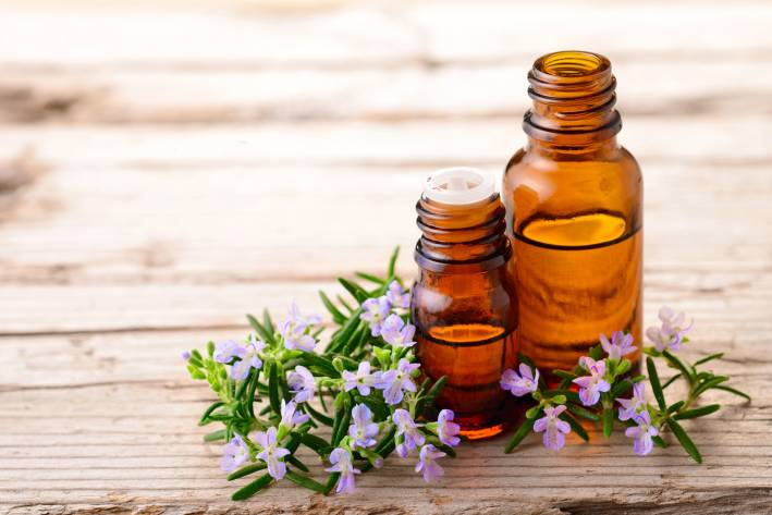 Blooming rosemary sprigs on a wooden table with essential oils in brown bottles.