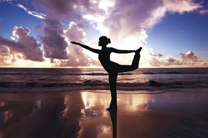 A woman doing yoga on the beach